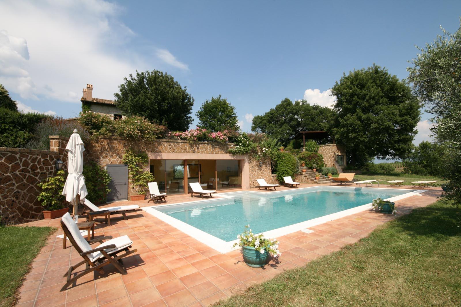 La bella piscina con l'ampio solarium e la casa di campagna in fondo