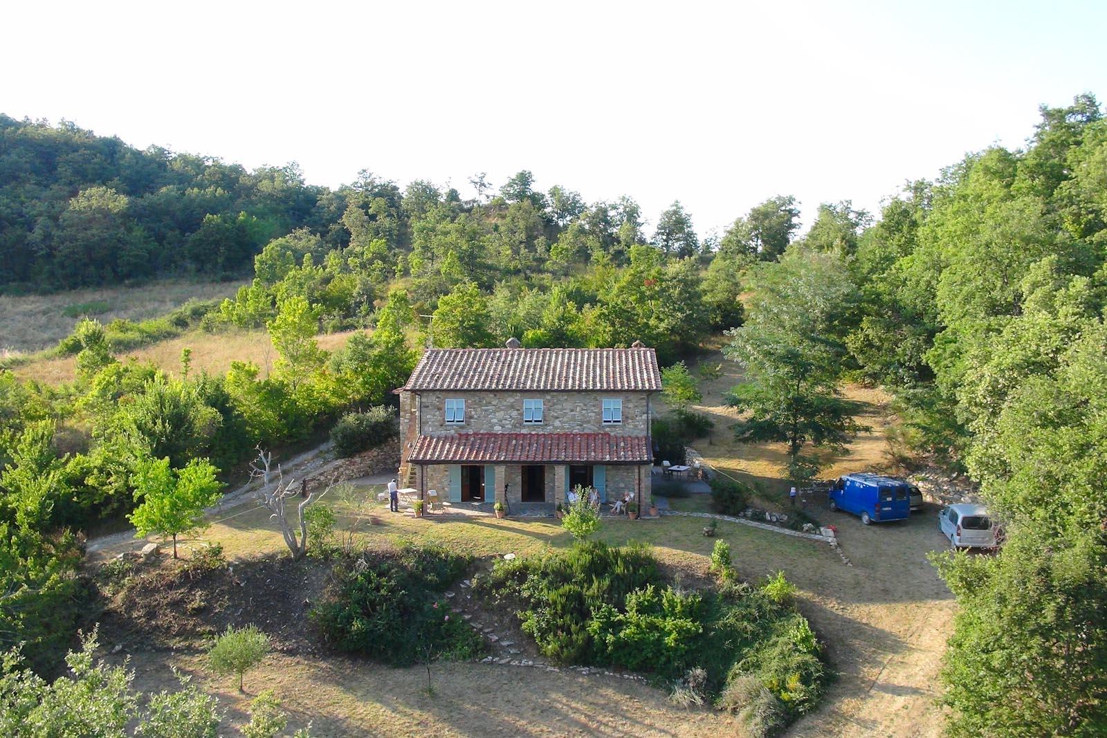 La casa di campagna con il portico e il giardino circostante