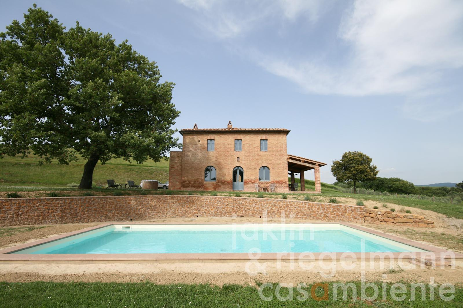 The thoroughly restored farmhouse for sale in the Crete Senesi with pool, olive grove and panoramic views