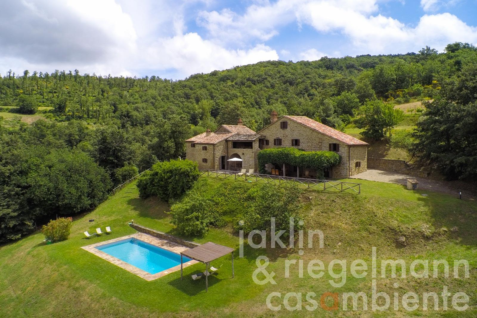 The traditional Tuscan stone farmhouse for sale with two independent houses, swimming pool and garden