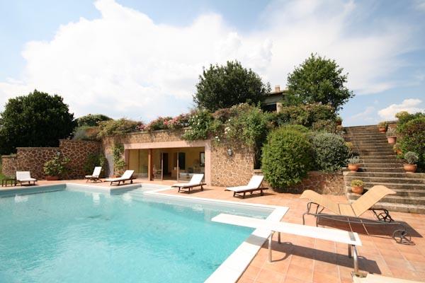 La piscina con la scalinata per accedere al giardino superiore e alla villa
