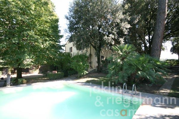 The view across the pool towards the Tuscan villa close to Florence for sale