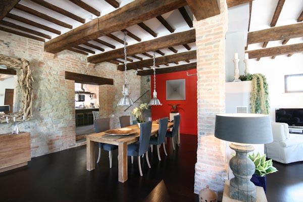 Il soggiorno con il camino comunicante al piano terra; la cucina moderna in fondo