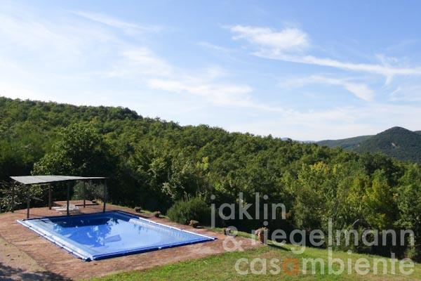 The pool with its surrounding terrace and panoramic views across the Umbrian hills