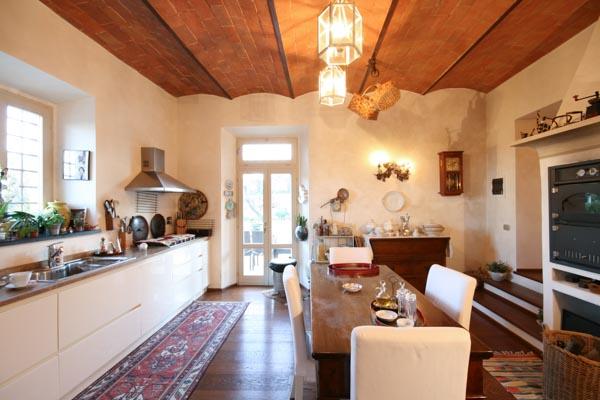 Die gemütliche Wohnküche mit offenem Kamin, Holzofen und Terracotta-Decke