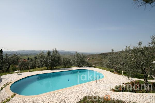 The swimming pool lined with Travertine and the panoramic view across the Tuscan hills