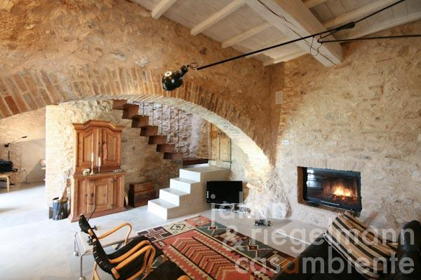 The comfortable living room with fireplace on the ground floor; the studio in the background