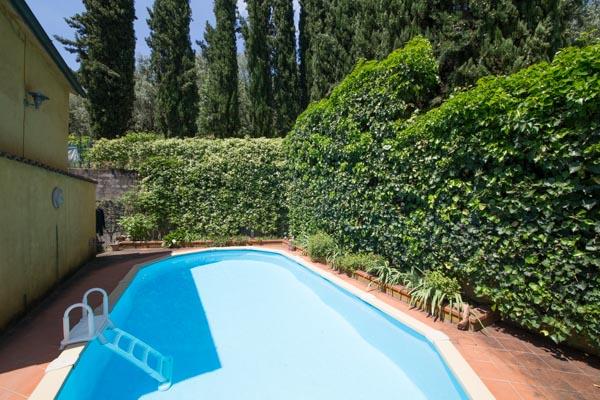 Der von Hecken und Zypressen eingerahmte Pool an der Nordseite des Hauses