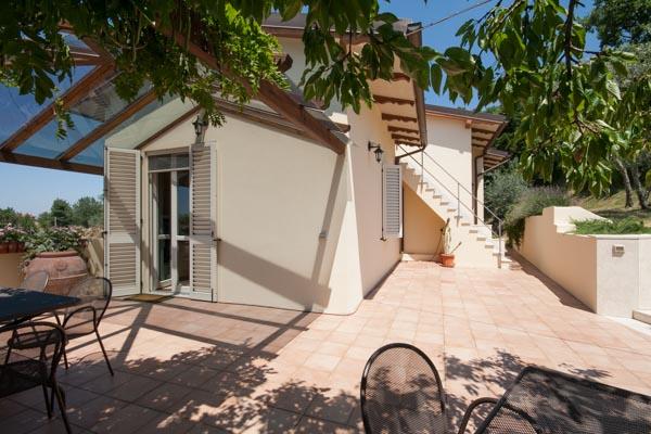 Die überdachte Terrasse vor der Küche im obersten Geschoss der Villa