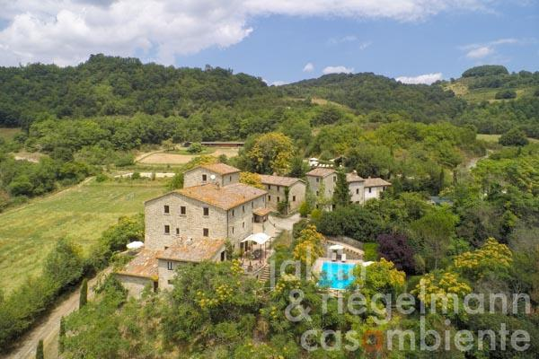 The restored medieval hamlet for sale in Umbria with four buildings, two pools, horse riding arena and stables
