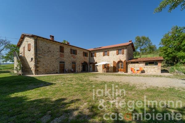 Typical Tuscan country house made of natural stone in panoramic position to the hills of the Casentino